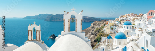Fototapeta Panoramic view of Oia town with traditional and famous houses and churches with blue domes over the Caldera on Santorini island. Greece. obraz