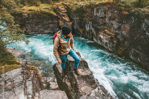 Adventurer man hiking alone active lifestyle extreme vacations outdoor on cliff Wallpaper Mural