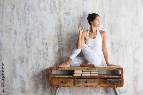 Fotografie, Obraz  Slim beautiful young woman yoga instructor doing asana sitting on a vintage console against the background of a concrete wall