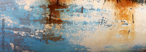 Abstract background of a decaying old wooden blue boat panel with patches of white and brown showing through the fading paint.