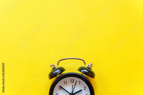 Photo Ringing twin bell vintage classic alarm clock Isolated on yellow colourful trendy background