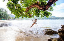 Beautiful Young Woman Traveler Swinging On A Swing On A Tropical Island In The Background Of Amazing Landscape