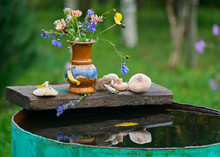 Autumn Still Life In The Country Bouquet Of Flowers And Wild Mushrooms On A Barrel Of Water.