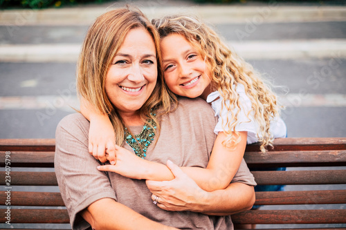 Fotografie, Obraz  mommy and daughter hugging with love and happiness together on a bench in outdoo