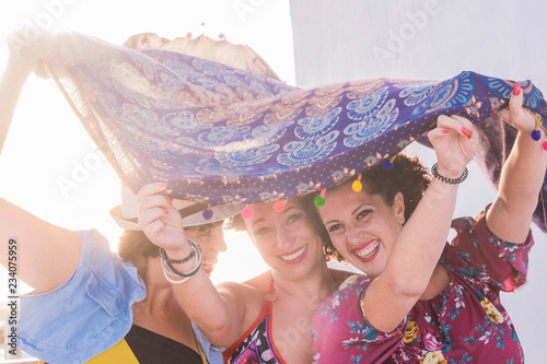 Fotografie, Obraz  three young women have fun together playing with the wind and laughing a lot hav