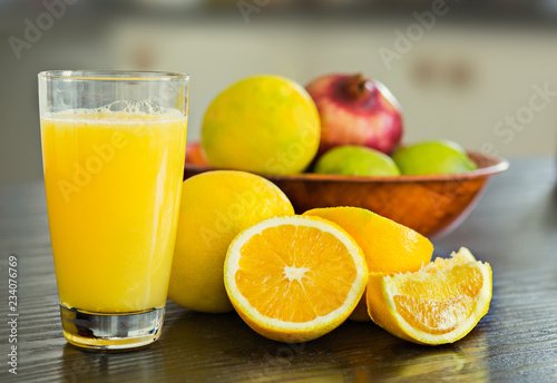 Glass of freshly squeezed orange juice with bowl of fruits on the background.
