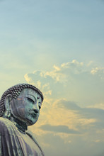 A Superimposed Or Double Exposures Of The Great Buddha Of Kamakura Town, Japan, A Bronze Statue OfAmida Buddha With A Beautiful Dramatic And Peaceful Clouds And Sky.