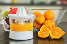 Juicer With Freshly Squeezed  Orange Juice And Whole And Sliced Oranges.