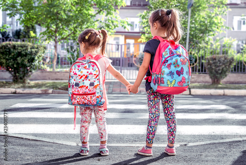 Fotografering Children go to school, happy students with school backpacks and holding hands to