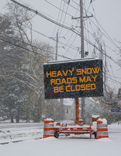 Electric Road Traffic Mobile Sign By The Side Of A Snow Covered Road With Snow Falling Warning Of Heavy Snow Alert And Roads May Be Closed.