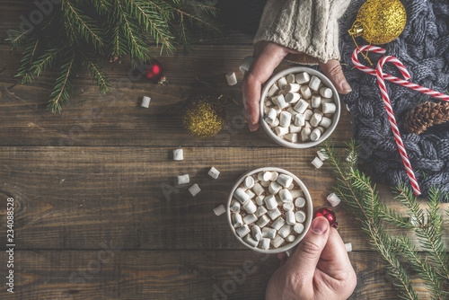 Foto auf AluDibond Schokolade Winter party concept with hot chocolate, two hands with cocoa cups with marshmallow on wooden table with christmas decorations, top view layout copy space