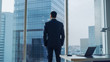 canvas print picture - Back View of the Thoughtful Businessman wearing a Suit Standing in His Office, Hands in Pockets and Contemplating Next Big Business Deal, Looking out of the Window. Big City Panoramic Window View.