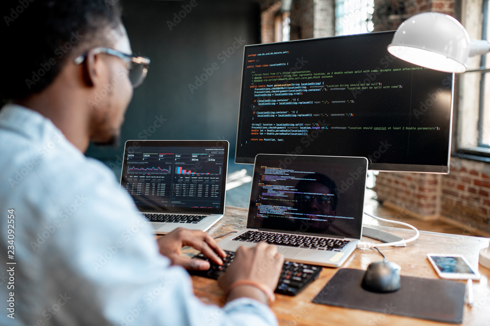 Fototapeta Young african male programmer writing program code sitting at the workplace with three monitors in the office. Image focused on the screen
