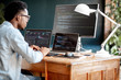 canvas print picture - Young african male programmer writing program code sitting at the workplace with three monitors in the office. Image focused on the screen