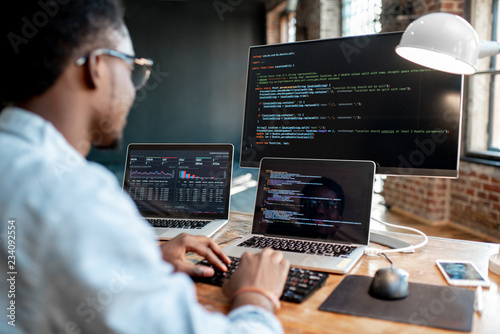 Fotografía  Young african male programmer writing program code sitting at the workplace with three monitors in the office