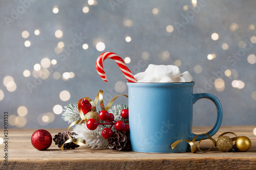 Winter lifestyle with cup of hot cocoa with marshmallows and Christmas decoration on wooden background. Bokeh effect.