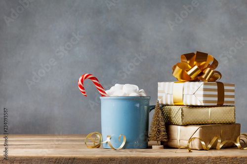 Winter lifestyle with cup of hot cocoa with marshmallows and Christmas gift or present boxes and holiday decorations on wooden background.