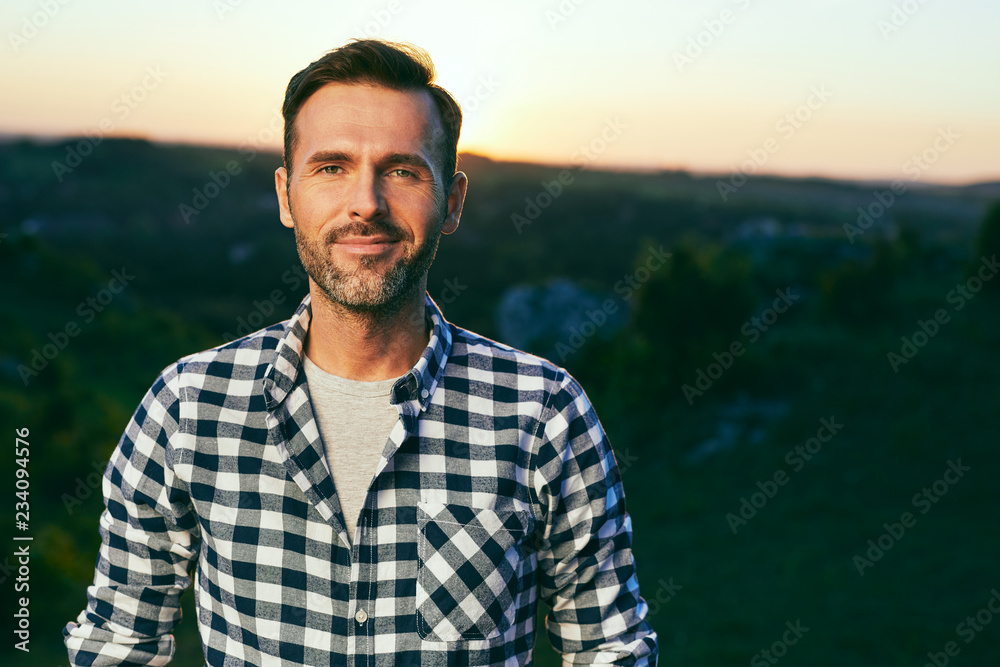 Fototapety, obrazy: Portrait of handsome man standing on meadow surrounded by nature