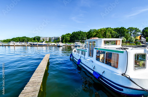 Houseboats and yachts are moored in Goehren-Lebbin (Germany) at a jetty of the lake Fleesensee