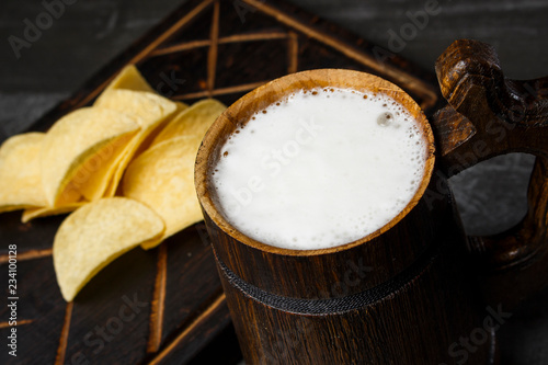 Tuinposter Bier / Cider Beer in a wooden mug with chips on the board