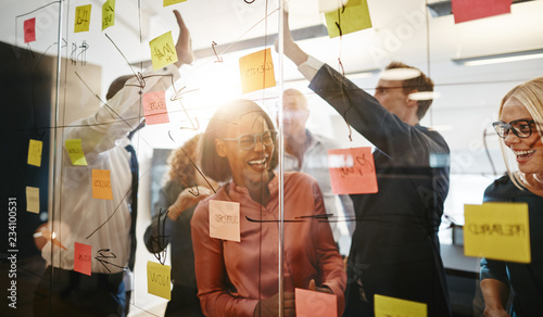Ecstatic group of businesspeople celebrating together after a br