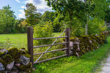 Rock Fence And A Wooden Gate A...