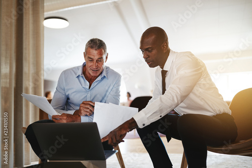 Photo Two diverse businessmen discussing work together in an office