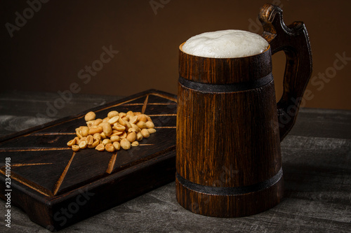 Tuinposter Bier / Cider Beer in a wooden mug with peanuts on the board