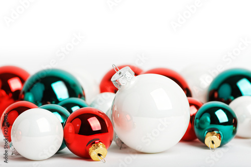 Closeup colorful christmas balls of different sizes on white background. Shallow focus. Copyspace.