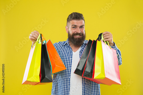 Fényképezés  Man bearded hipster cheerful face carry paper shopping bags on yellow background