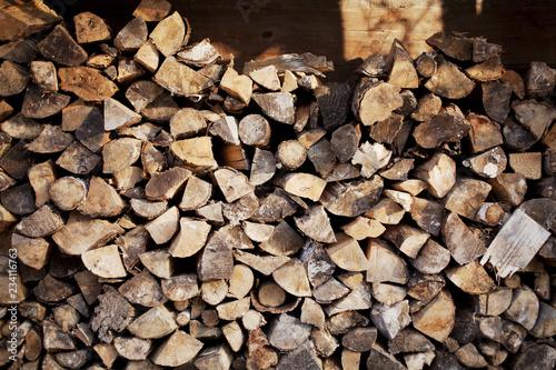 Fototapeta Porąbane polana drewniane na opał złożone przy ścianie stodoły szopy  - Drewno na opał obraz