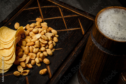 Tuinposter Bier / Cider Beer in a wooden mug with peanuts and chips on a board