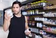 Leinwandbild Motiv Young muscular sportman looking sport dietary supplements in store