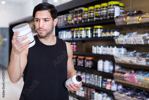 Fotografia  Young muscular sportman looking sport dietary supplements in store