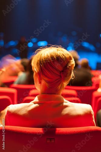 Fotomural Jeune femme blondede dos assise dans salle de spectacle