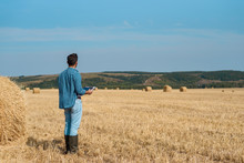Man Farmer Agronomist In Jeans And Shirt Stands Back In The Field After Haymaking, With Tablet Looking Into The Distance. Rural Business, Agricultural Industry, Freedom After Work, Concept