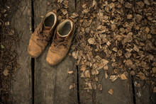 A Pair Of Nubuck Hiking Boots On Wooden Floor With Dead Leaves Ang Twigs. Top View, Empty Space