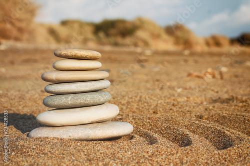 Photo sur Plexiglas Zen pierres a sable Stones pyramid balance on sand and blurred background. Spa therapy theme. Sea view. Beach. Zen garden.