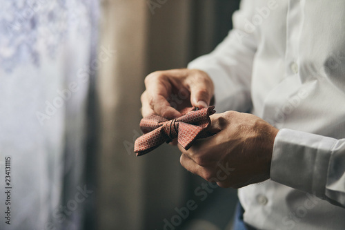Fotografía  businessman putting on  bow tie,man butterfly clothes,groom getting ready in the