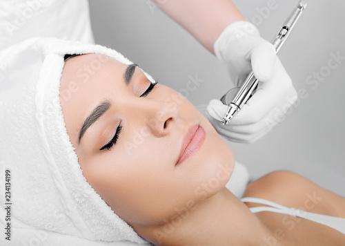 Fotografia  face of beautiful woman while procedure jet peeling, facial treatment