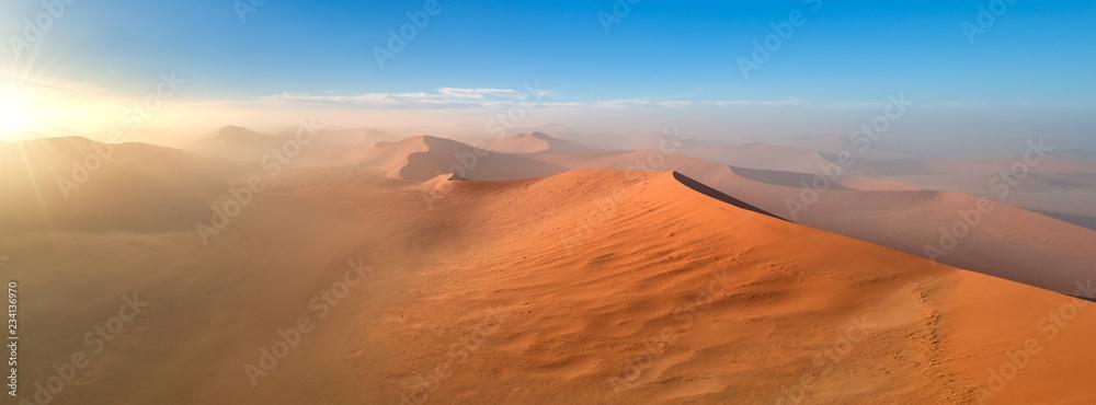 Fototapety, obrazy: Panoramic, aerial, artistic photo of Namib dunes.  Early morning Namib desert covered in mist. Orange dunes of Namib from above. Desert landscape. Sunrise in Namib-Naukluft  desert. Traveling Namibia.
