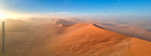 Obraz Panoramic, aerial, artistic photo of Namib dunes.  Early morning Namib desert covered in mist. Orange dunes of Namib from above. Desert landscape. Sunrise in Namib-Naukluft  desert. Traveling Namibia. - fototapety do salonu