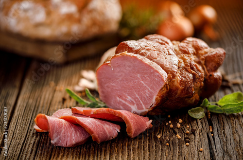 Smoked meat, Sliced smoked gammon on a wooden  table with addition of fresh  herbs and aromatic spices.   Natural product from organic farm, produced by traditional methods
