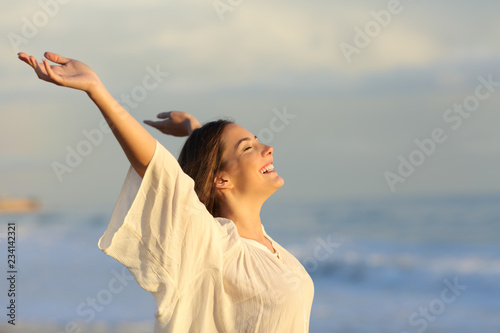 Obraz Joyful woman enjoying a day on the beach - fototapety do salonu