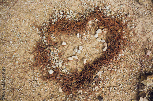 Fotografering Heart of pebbles inlaid on a background of sand