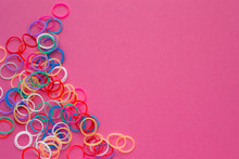 Rainbow Loom Bands Bracelets On Pink Background. Colorful Ties For Waving Hair. Children Hobby - Handmade Bracelets.