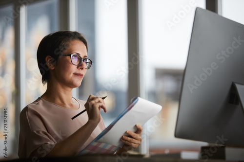 Cuadros en Lienzo Confident businesswoman with document looking at computer screen and making work