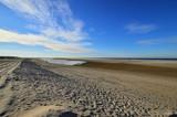 Fototapeta Fototapety z morzem do Twojej sypialni - Nadmorskie wybrzeże, plaża i morze pod niebieskim niebem z chmurami.