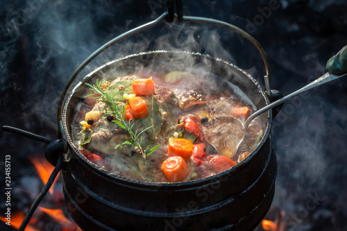 Hot and yummy hunter's stew on bonfire