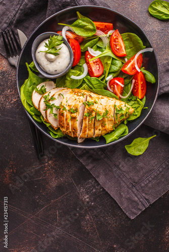 Fotografie, Obraz  Grilled chicken breast salad with spinach, tomatoes and Caesar dressing, dark background